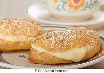 Creamy Eclairs - Eclairs with powdered sugar on top on a...