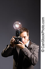 Retro photo journalist holding vintage camera with flash...