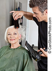 Hairdresser Blow Drying Woman's Hair - Male hairdresser blow...