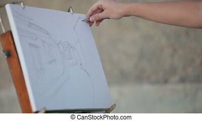 sketch - woman's hand drawing with a pencil street scene