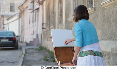 Painter at work - woman drawing in pencil using easel on a...
