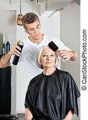 Woman With Hairdresser Styling Hair At Salon