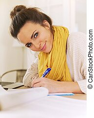 Smiling Woman Indoor Writing on Her Notepad