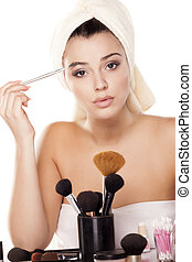eyebrows combing - girl with towel on head combing her...