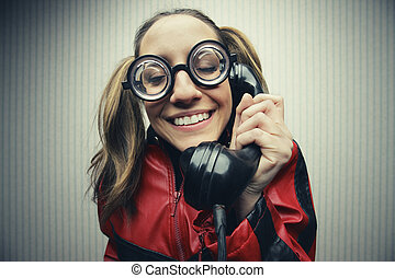 Nerdy woman speaking on a black rotary vintage phone - funny...