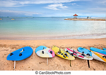 Surf boards on idyllic tropical sand Nusa Dua beach, Bali,...
