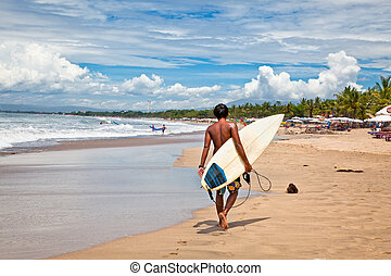 Young man with surf board on beach in Bali, Indonesia. -...