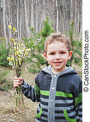 Boy with willow - Spring boy stands in a forest and holds a...
