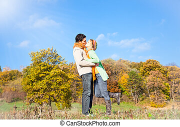 Young beautiful couple are kissing in the autumn park