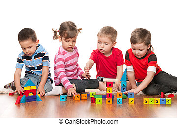 Four kids are playing on the floor