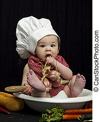 Chef Baby in Bowl - Cute baby wearing a chefs apparel while...