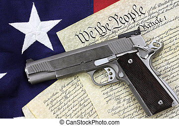 Gun and Constitution - Handgun lying over a copy of the...
