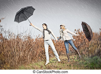 Woman and man with umbrellas during strong wind - Woman and...