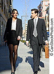 Portrait of an atractive business people walking on the...