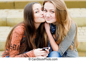 Friends comfort - Teenage girl comforting her friend reading...