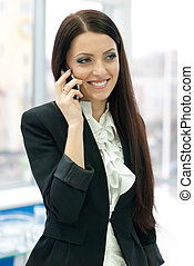 Young successful business woman speaking on mobile