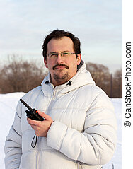 Man with cb radio outdoors winter day.