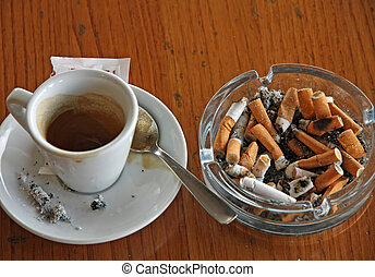cup of coffee espresso and ashtray chock full of cigarette butts