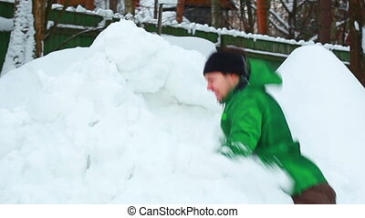Young man fighting with pile of snow