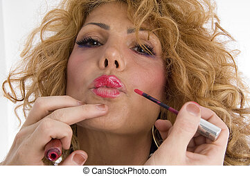 beautician doing lip make up of woman on an isolated...