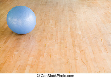 Swiss ball with copyspace - Swiss ball on a wooden gym floor...