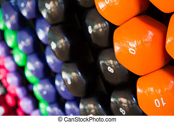 Dumbbells - Closeup of multicolored dumbbells in a gym