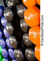 Dumbbells - Closeup of multicolored dumbbells in a fitness...