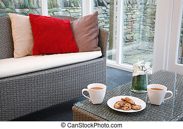 Conservatory interior design with rattan chairs and coffee...