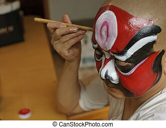 a chinese opera actor is painting his face before the performanc