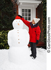Person building snowman - An Asian girl building a real...