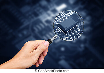 Hand holding magnifying glass with computer chip