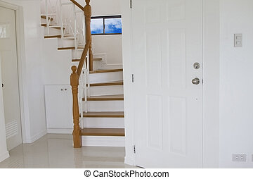 Wood stairs, interior on white external coating of walls.