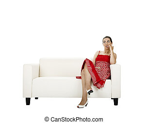 Biting her nails - Beautiful woman seated on a white couch...