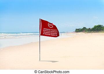 Red flag on the sand beach