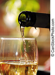 Glass of white wine - pour wine from green bottle into glass