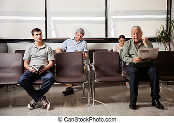 People Waiting In Hospital Lobby - Multiethnic people...