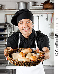 Male Chef Offering Breads In Kitchen - Portrait of male chef...