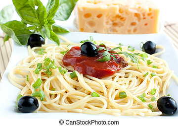 spaghetti with olives and tomato sauce on a white plate