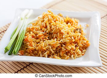 Rice with green onions and brown bread on a white square...