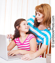 Young woman with girl using laptop computer