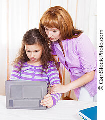 Young woman with girl using tablet computer