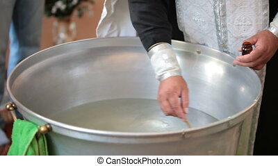 priest blesses baptismal font before the christening