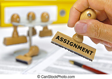 assignment - rubber stamp in hand marked with assignment