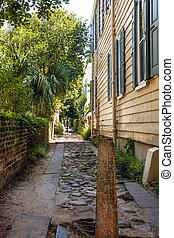 Alley by Old Wood Siding House - An alley by an old wood...