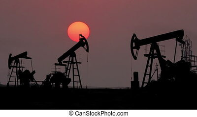 working oil pumps silhouette against timelapse sunset