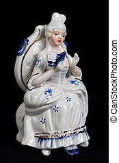 porcelain figurine in the form of a girl in medieval dress sitting on a chair isolated on a black background
