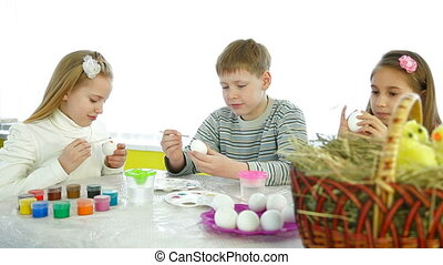 Kids Painting Easter Eggs - Three children painted Easter...