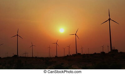 wind farm - turning windmills against timelapse sunset
