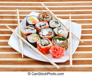 Sushi rolls on the plate with chopsticks