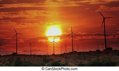 wind farm - turning windmills against timelapse sunrise